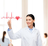 Smiling female doctor pointing to cardiogram Stock Images