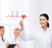 Smiling female doctor pointing to cardiogram. Healthcare, medicine and technology concept - smiling female doctor pointing to heart and cardiogram stock photo