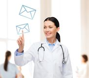 Smiling female doctor pointing to envelope Stock Photos
