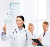 Smiling female doctor pointing to envelope Stock Photography