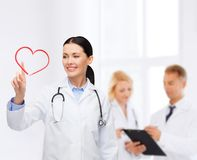 Smiling female doctor pointing to heart Stock Images