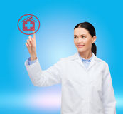 Smiling female doctor pointing to hospital sign Stock Photos