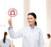 Smiling female doctor pointing to hospital sign Royalty Free Stock Image