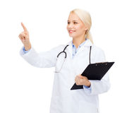 Smiling female doctor pointing to something Stock Photo