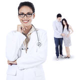 Smiling female doctor and pregnant couple Stock Image