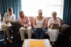 Smiling female doctor reading book by senior people sitting on sofa against window. At retirement home Royalty Free Stock Image