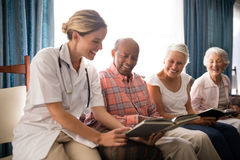 Smiling female doctor reading book to senior people sitting on furniture against window. At retirement home Stock Photography