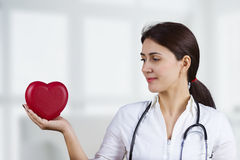 Smiling female doctor with red heart and stethoscope Royalty Free Stock Photo