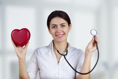 Smiling female doctor with red heart and stethoscope royalty free stock images