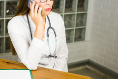 Smiling Female Doctor Relaxing at her Office While Calling to Someone Using a Mobile Phone close-up. Royalty Free Stock Photos