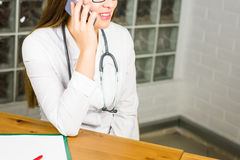 Smiling Female Doctor Relaxing at her Office While Calling to Someone Using a Mobile Phone close-up. Stock Photo