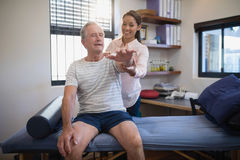 Smiling female doctor and senior male patient looking at hand Stock Photography