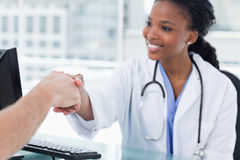 Smiling female doctor shaking a hand stock photography