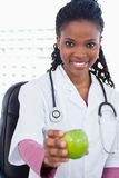 A smiling female doctor showing an apple. Portrait of a smiling female doctor showing an apple in her office Royalty Free Stock Photo