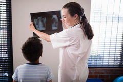 Smiling female doctor showing x-ray to boy against wall Stock Photography