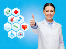 Smiling female doctor showing thumbs up Royalty Free Stock Images