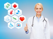 Smiling female doctor showing thumbs up Stock Photo