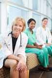 Smiling female doctor sitting with smiling female nurses Stock Photos