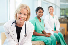Smiling female doctor sitting with smiling female nurses Stock Photo