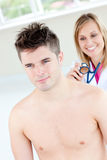 Smiling female doctor sounding her male patient Royalty Free Stock Images