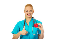 Smiling female doctor with stethoscope holding heart model and showing thumb up Stock Images