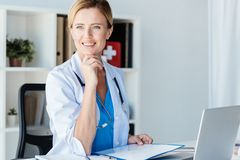 smiling female doctor with stethoscope looking away at table with clipboard and laptop stock image