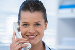 Smiling female doctor talking on telephone. Portrait of smiling female doctor talking on telephone in clinic Stock Photos
