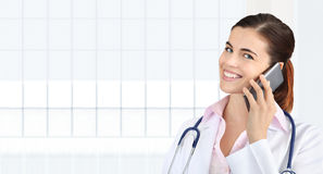 Smiling female Doctor talks to the cell phone, concept of medical worker. Isolated on white stock images