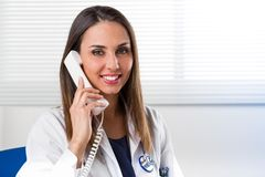 Smiling female Doctor with telephone to ear. Attractive young smiling female Doctor with stethoscope around neck sat at desk with telephone to ear Stock Photo