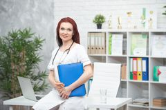 Smiling female doctor in uniform with a stethoscope and a blue folder in her hands is standing in his medical office and meets royalty free stock photo