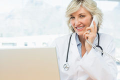 Smiling female doctor using laptop and phone Stock Image