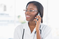 Smiling female doctor using mobile phone Royalty Free Stock Photography