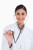 Smiling female doctor using stethoscope Royalty Free Stock Photos