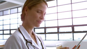 Smiling female doctor using tablet. At hospital stock footage