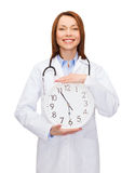 Smiling female doctor with wall clock Stock Photography