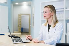 Smiling female doctor wearing a scrub and working at the hospital reception, she is writing a medical report on a. Clipboard and scheduling appointments royalty free stock photography