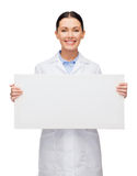 Smiling female doctor with white blank board. Healthcare, advertisement and medicine concept - smiling female doctor with white blank board Royalty Free Stock Images