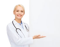 Smiling female doctor with white blank board Stock Photography