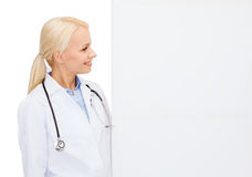 Smiling female doctor with white blank board. Healthcare, advertisement and medicine concept - smiling female doctor with white blank board Stock Images