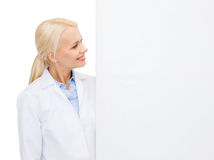 Smiling female doctor with white blank board. Healthcare, advertisement and medicine concept - smiling female doctor with white blank board Stock Image