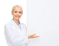Smiling female doctor with white blank board Stock Image