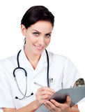Smiling female doctor writing on a clipboard Stock Images