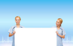 Smiling female doctors or nurses with blank board Royalty Free Stock Image
