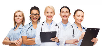 Smiling female doctors and nurses with stethoscope. Healthcare and medicine concept - smiling female doctors and nurses with stethoscope Stock Image