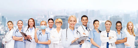Smiling female doctors and nurses with stethoscope. Healthcare and medicine concept - smiling female doctors and nurses with stethoscope Royalty Free Stock Photos