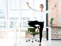 Smiling female doing gymnastics at work Royalty Free Stock Photography