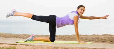Smiling female doing yoga poses sitting on sunny beach Stock Images