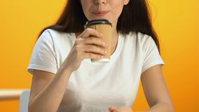 Smiling female drinking flavored tea from carton cup, enjoying taste of beverage. Stock footage stock video footage