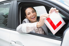 Smiling female driver tearing up her L sign Stock Image