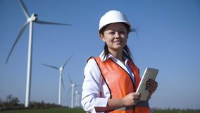 Smiling female engineer standing against wind farm Stock Photos